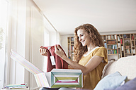 Smiling woman at home sitting on couch unpacking parcel with garment - RBF003086