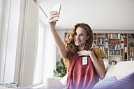 Smiling woman at home taking a selfie with new garment - RBF003130