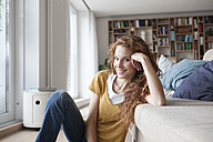 Smiling woman at home sitting on floor - RBF003105