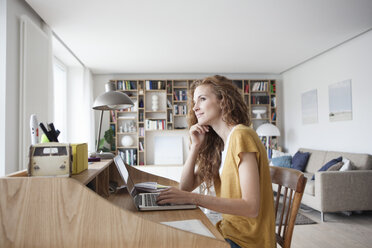 Woman at home using laptop on secretary desk - RBF003110