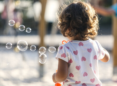 Back view of little girl making soap bubbles at playground - MGOF000479