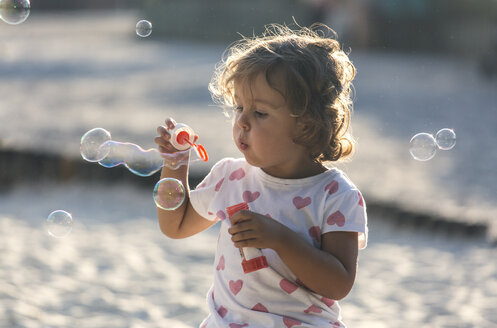 Little girl making soap bubbles at playground - MGOF000480
