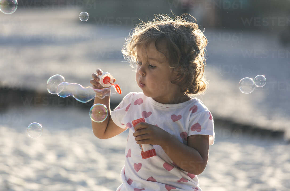 Little girl making soap bubbles at playground - MGOF000480 - Marco Govel/Westend61