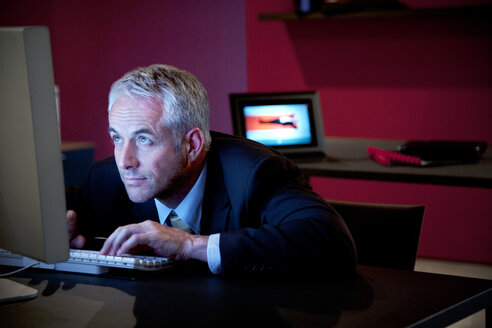 Businessman sitting at desk using computer - TOYF001164