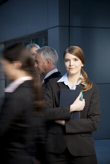 Smiling businesswoman holding file with businesspeople passing by - TOYF001235