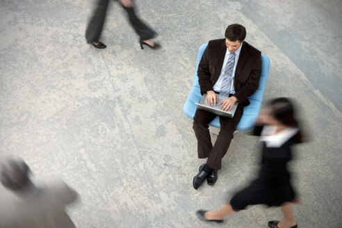 Businessman using laptop with people passing by - TOYF001241