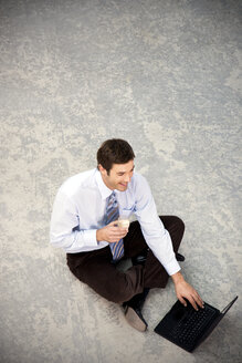 Smiling businessman sitting on floor using laptop - TOYF001244