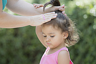 Mother tying hair of her little daughter - ERLF000025