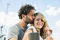 Smiling couple outdoors taking a selfie - FMKF001849