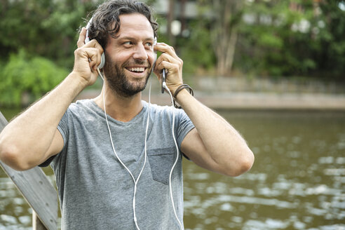 Happy man listening to music at the waterside - FMKF001892