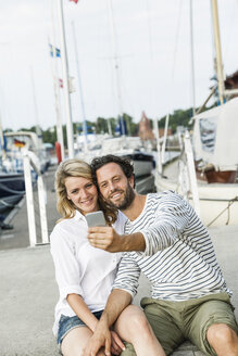 Germany, Luebeck, smiling couple at marina taking a selfie - FMKF001856