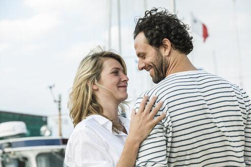 Germany, Luebeck, smiling couple at marina - FMKF001859