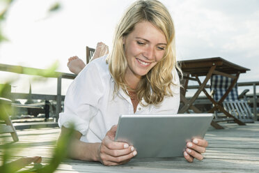 Smiling young woman relaxing on deck using digital tablet - FMKF001862