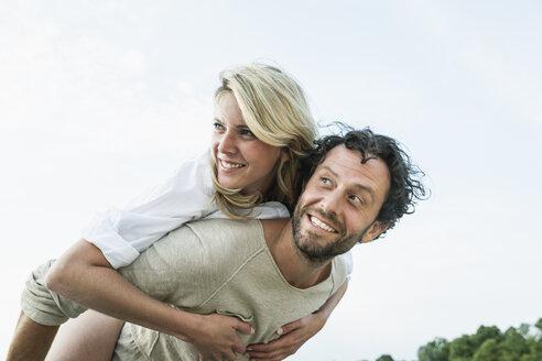 Smiling man carrying woman piggyback - FMKF001871