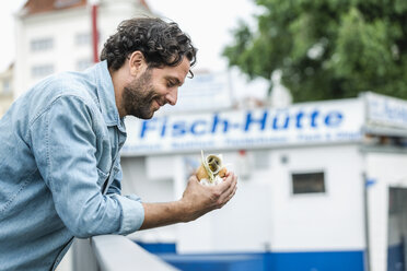 Smiling man holding a fish sandwich - FMKF001877