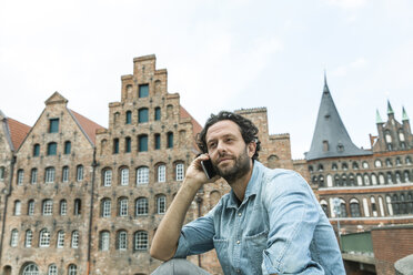 Germany, Luebeck, man on cell phone in the city - FMKF001886