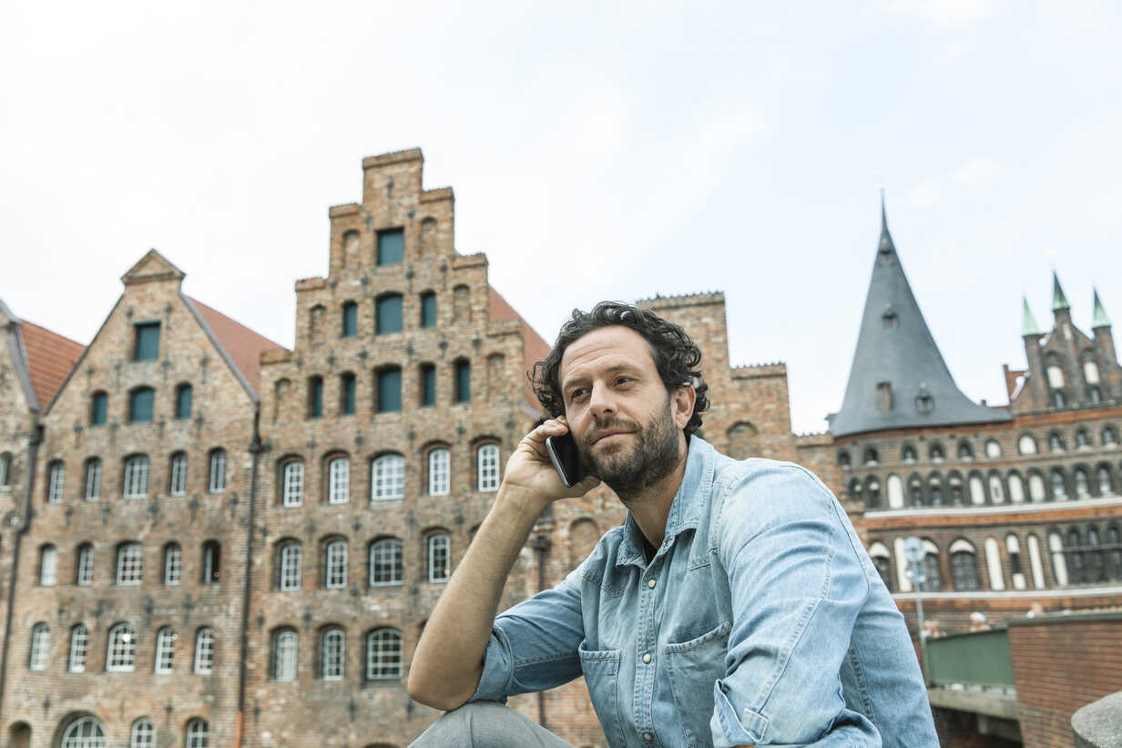 Germany, Luebeck, man on cell phone in the city - FMKF001886 - Jo Kirchherr/Westend61