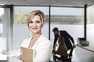 Portrait of smiling businesswoman in office - ZEF007158