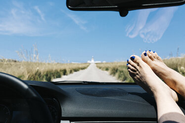 Spain, Menorca, feet on the dashboard, driving on empty road on vacations with a lighthouse in the background - JRFF000004