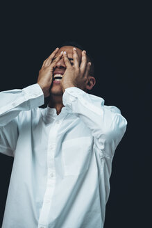Laughing young man wearing white shirt with hands on his face in front of black background - CHAF001368