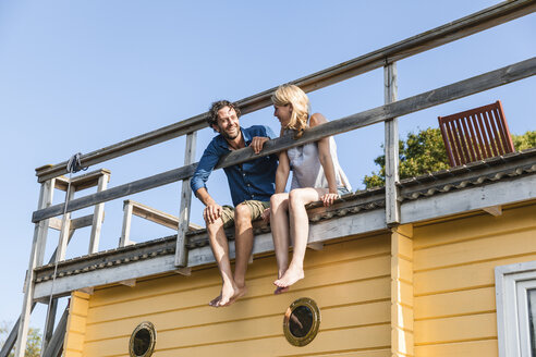 Couple sitting on roof deck of a house boat - FMKF001934