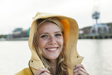 Portrait of young woman wearing rain coat at the waterside - FMKF001954