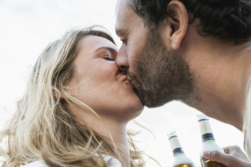 Couple with beer bottles kissing outdoors - FMKF001957