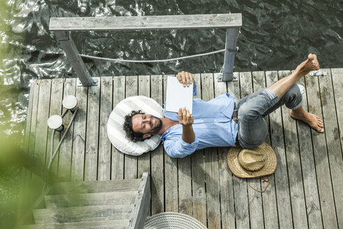 Man lying on platform at the waterside holding digital tablet - FMKF001969