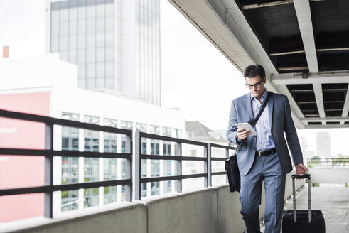 Businessman on business trip looking at his mini tablet - UUF005352