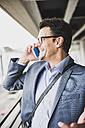 Smiling businessman telephoning with smartphone - UUF005357