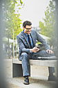 Businessman sitting on a bench looking at his smartphone - UUF005371