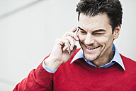 Portrait of smiling businessman wearing red pullover telephoning with smartphone - UUF005381