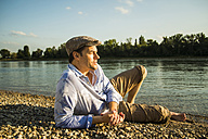 Man wearing cap relaxing at riverside in the evening twilight - UUF005393