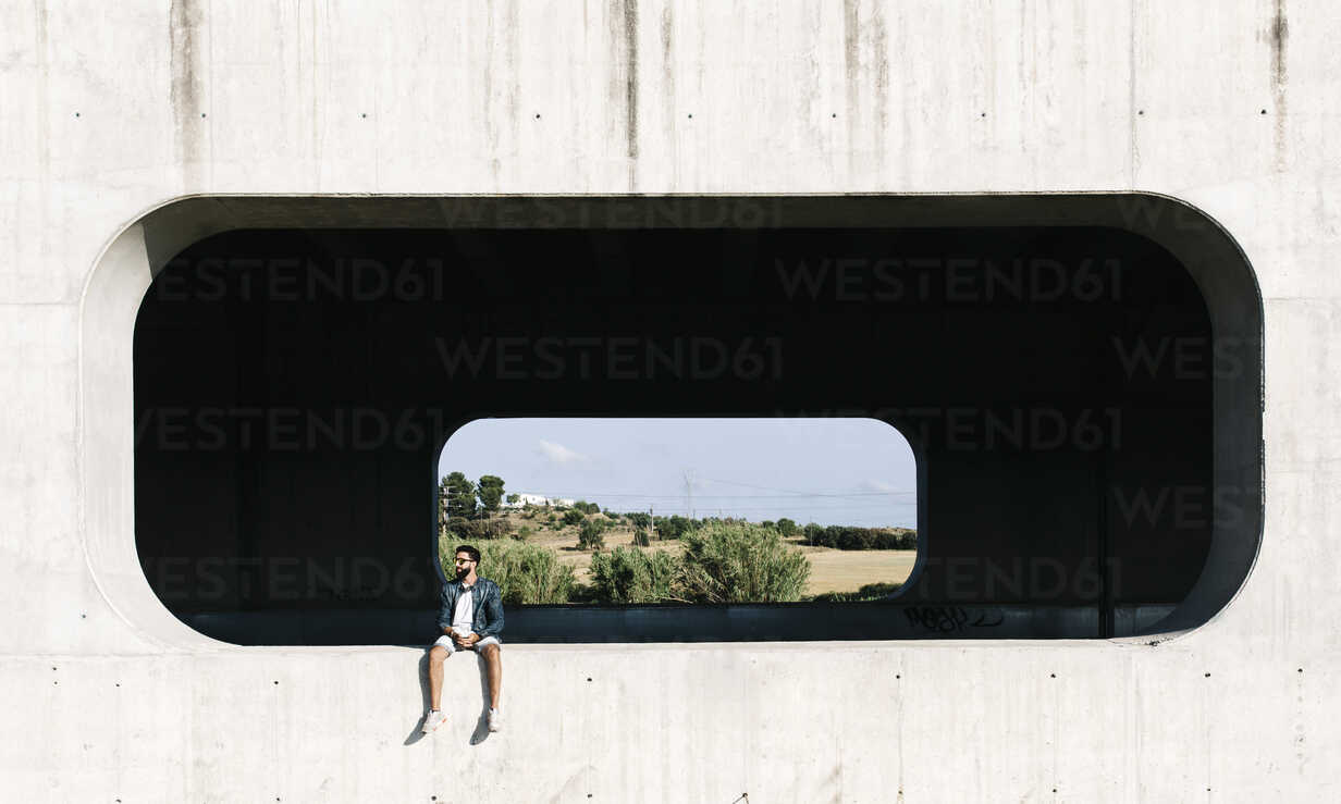 Spain, Tarragona, young man sitting in niche of a concrete wall - JRFF000007 - Josep Rovirosa/Westend61