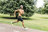 Athletic young man jogging in the park - MGOF000488