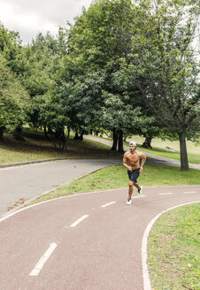 Athletic young man jogging in the park - MGOF000491