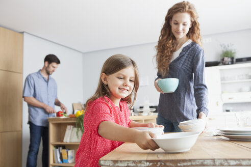 Smiling little girl laying the table in the kitchen with her parents in the background - RBF003367