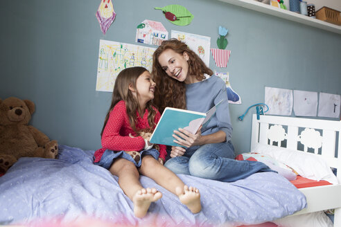 Mother and little daughter sitting together on bed in children's room with a book - RBF003375