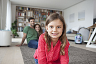 Portrait of smiling little girl and her parents in the background in the  living room - RBF003390