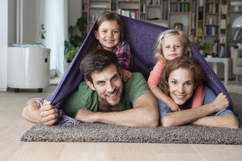 Portrait of couple with her little daughters lying together on the floor of the living room covered by a blanket - RBF003395