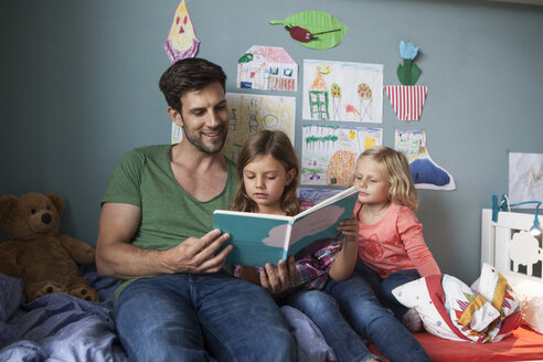 Father and his little daughters sitting together on bed in children's room reading a book - RBF003400