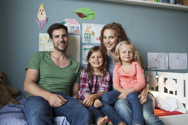 Family picture of couple with her little daughters sitting together on bed in children's room - RBF003402