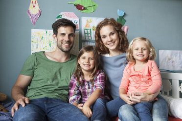 Family picture of couple with her little daughters sitting together on bed in children's room - RBF003403