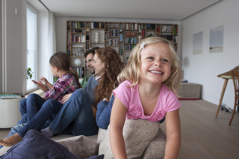 Portrait of smiling little girl on the backrest of couch with her family sitting in the background - RBF003419
