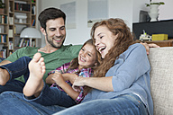Happy couple and little daughter on the couch at home - RBF003424