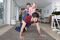 Man playing with his little daughters  in the living room - RBF003428