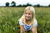 Portrait of girl kneeling on a meadow watching something - MGOF000500