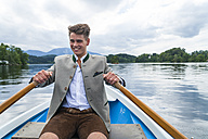 Germany, Bavaria, portrait of smiling young man rowing on Staffelsee - TCF004851