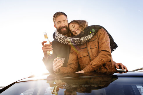 Happy couple looking through sunroof of a car sharing a scarf - PESF000169