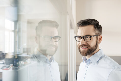 Smiling businessman looking through glass wall - PESF000060